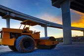 stock photo of bulldozer  - bulldozer tank road construction machine against dusky sky and infra construction of express way - JPG