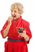 Pretty senior woman eating a bowl of healthy delicious mixed berries.  Isolated on white.