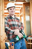 Handsome construction worker with his tool belt, holding a drill.