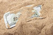 foto of 100 dollars dollar bill american paper money cash stack  - 100 dollar bill buried in the sand - JPG