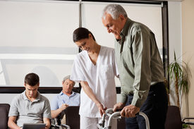 stock photo of zimmer frame  - Senior man being assisted by female nurse to walk the Zimmer frame with people sitting in background - JPG