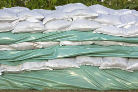 picture of tarp  - Wall of sandbags and tarp for flood protection - JPG