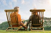 Rear View Of Mature Couple Sitting On Lounge Chair Holding Hands Conteplate the Future