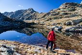 Male hiker standing in front of a mountain lake. Autumn sunny day, italian Alps, Europe..
