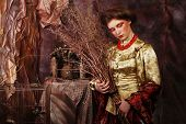 foto of witch ball  - young woman wearing ball dress with bright make up holding  dry branches - JPG