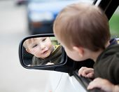 picture of mirror  - Small child looking to outside mirror in the car - JPG