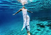 Young female swimming underwater, enjoying nice refreshing water, wearing long dress, summer vacation and travel concept