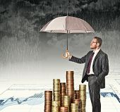 businessman cover his money with umbrella