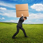 tired young businessman in suit carrying two heavy boxes at outdoor