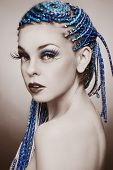 Sepia coloured portrait of young beautiful girl with blue braids and huge fancy fake eyelashes