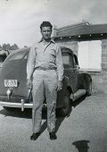 CANADA - CIRCA 1940s: Vintage photo shows young man standing near his car.