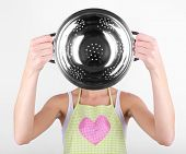 Cooker holding metal colander on light background