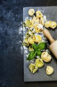 Homemade raw Italian tortellini and basil leaves on dark vintage background