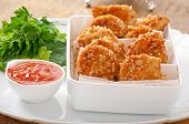 Chicken nuggets coated in cereals, crumbs and sesame