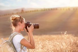 picture of track field  - Happy traveler girl photographing ripe wheat field in bright sun rays - JPG
