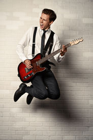 stock photo of rocking  - Expressive young man playing rock - JPG