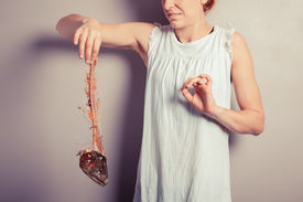 picture of disgusting  - A disgusted young woman is holding a fish skeleton - JPG