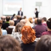 stock photo of entrepreneurship  - Speaker at Business Conference and Presentation. Audience in the conference hall. Business and Entrepreneurship. Copy space on white screen.