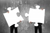picture of comrades  - Two business people assembling blank white jigsaw puzzles with concrete wall background - JPG