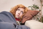 pic of lonely woman  - Sad lonely redhead woman looking up and resting on the sofa at home - JPG