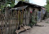 pic of log fence  - A rural home in a small village in Honduras is protected by a handmade stick and barbed wire fence. A red piece of clothing tied on a post catches the viewer