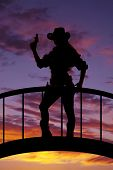 picture of pistols  - a silhouette of a woman standing on a bridge with a pistol in her hand - JPG