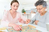 stock photo of indoor games  - Elderly woman playing a board game - JPG