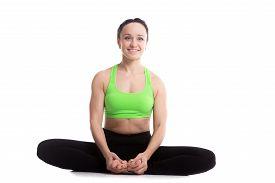 picture of ashtanga vinyasa yoga  - Happy smiling sporty girl doing yoga training bound angle posture baddha konasana cobbler pose - JPG