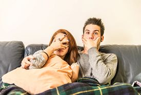 stock photo of horror  - Couple watching horror movie on television on the couch - family,recreation,leisure,togetherness concept
