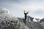 stock photo of spyglass  - Young woman engineer on rock top looking in spyglass - JPG