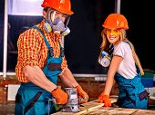 stock photo of gas mask  - Man in gas mask and woman in builder helmet with electric planer - JPG