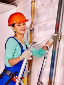 picture of millwright  - Woman in builder uniform on ladder  indoor - JPG