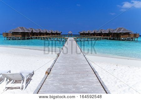 poster of Beautiful tropical Maldives resort hotel with beach and blue water for relax. Maldives beach on cute island. White sand beach with a coral reef. Best beach for relaxation, sunbathing and snorkeling.