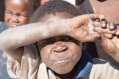 NAMIBIA - 6 de mayo: Un niño africano no identificado cubre sus ojos contra el caliente sol 06 de mayo de 2007 en Ka cerca