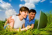 Casual happy couple on a laptop computer outdoors. Lay on the green grass.