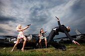 stock photo of revenge  - Two girls with arms shooting at guy - JPG