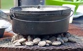 stock photo of dutch oven  - Dutch oven pot on charcoal cooking food - JPG