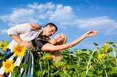 picture of love couple  - loving couple in a field of sunflowers - JPG