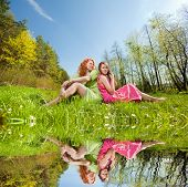 Mom and Daughter Having Fun. Specular reflection in the water.