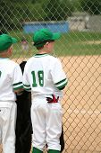 picture of little-league  - young baseball player watching the game while waiting for his turn to bat - JPG