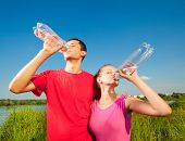 stock photo of drinking water  - Young love Couple drink water under blue sky - JPG