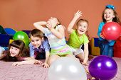 stock photo of preschool  - Happy preschool kids playing with balloons - JPG