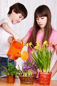 Zwei niedlichen Kinder Blumen gießen