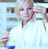 Closeup of a female researcher holding test tubes carrying out experiments in a lab