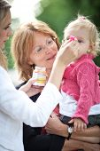 cute little girl outdoors in a park being fed apple pur?e by her mom and held by her grandmother (shallow DOF, selective focus)