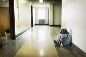 stock photo of forlorn  - Depressed young boy sitting in the hall - JPG