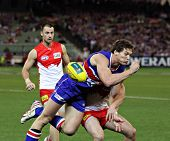 MELBOURNE - SEPTEMBER 12: Will Minson is tackled in the AFL second semi final - Western Bulldogs vs