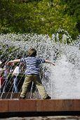 A Boy At A  Fountain