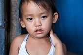 Portrait of an adorable Filipino girl living in poverty. Natural light.