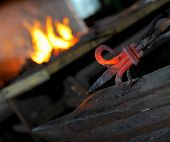 pic of blacksmith shop  - Blacksmith forges a red - JPG